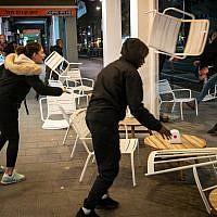 Ethiopian-Israeli protesters trash a sidewalk cafe on Ibn Gabriol Boulevard in Tel Aviv, January 30, 2019. (Luke Tress/Times of Israel)