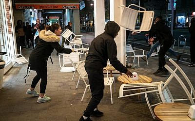 Ethiopian-Israeli protesters trash a sidewalk cafe on Ibn Gabriol Boulevard in Tel Aviv, January 30, 2019. (Luke Tress/Times of Israel)