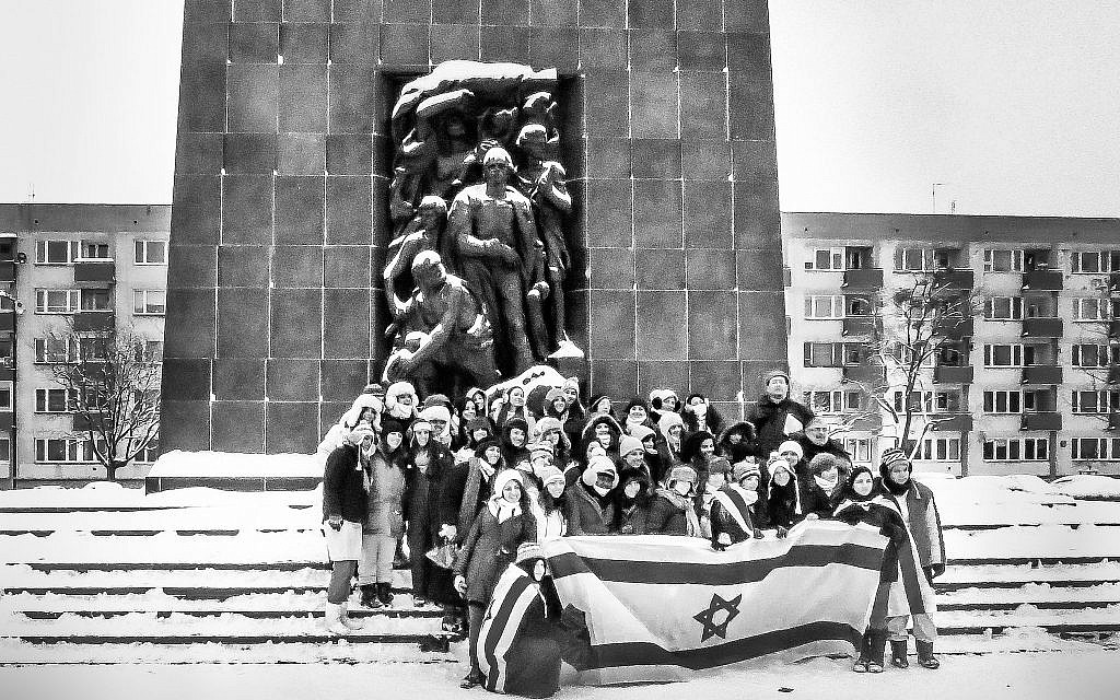 A group of Israeli school children, accompanied by an armed guard, pose with an Israeli flag before Natan Rapoport's 1948 Monument to the Ghetto Heroes to memorialize their visit and mark its meaning for the Israeli state. (Courtesy Walkowitz)