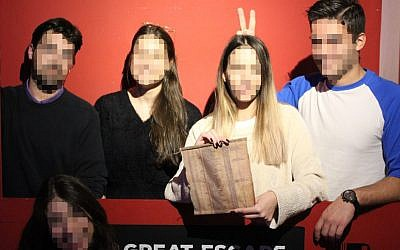 Visitors to a Schindler's List-style escape room in Thessaloniki smile with a list of 'innocents' they retrieved during the game (Facebook)