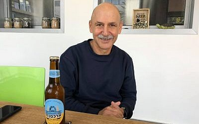 Ori Sagi with a bottle of 'Otef Aza' beer at the Alexander Beer brewery, January 3, 2019. (Renee Ghert-Zand/TOI)