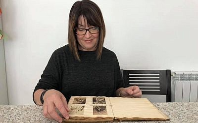 Karen Ievers looks at the Victorian-era photographs of Jane Austen's relatives in the album she bought on eBay. Jerusalem, January 24, 2019. (Renee Ghert-Zand/TOI)