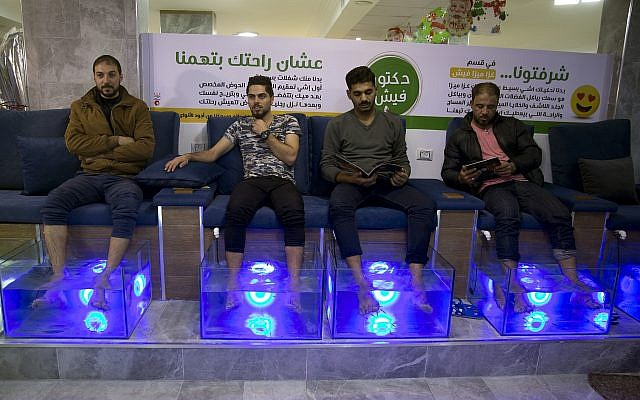 Palestinians soak their feet in tank stocked with fish at a cafe in Gaza City, December 26, 2018. (Khalil Hamra/AP)