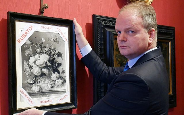 "In this photo made available on January 1, 2019, Eike Schmidt, director of the Uffizi Gallery, poses for a photo as he holds onto a copy of a still-life ""Vase of Flowers,"" by Dutch artist Jan van Huysum, with writing in red reading ""stolen,"" inside the Uffizi gallery, in Florence, Italy. (Uffizi Gallery press office via AP)"