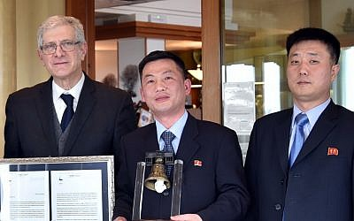 "This March 20, 2018 photo made available Thursday, January 3, 2019 by the Parish of Farra di Soligo, Italy, shows North Korea's acting ambassador to Italy Jo Song Gil, center, holding a model of ""Bell of Peace of Rovereto"" during a cultural event on the occasion of a visit of the North Korean delegation to the Veneto region, in San Pietro di Feletto, near Treviso, northern Italy. Jo Song Gil is flanked by Senator Valentino Perin, left, and an unidentified North Korean diplomat at right. (Parish of Farra di Soligo via AP)"