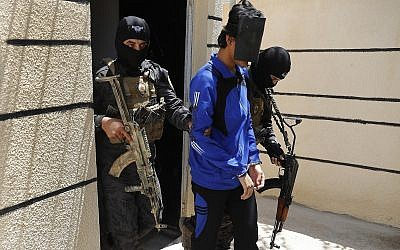 In this July 21, 2017, file photo, Kurdish soldiers from the Anti-Terrorism Units, carry a blindfolded an Indonesian man suspected of Islamic State membership, at a security center, in Kobani, Syria (AP Photo/Hussein Malla, File)