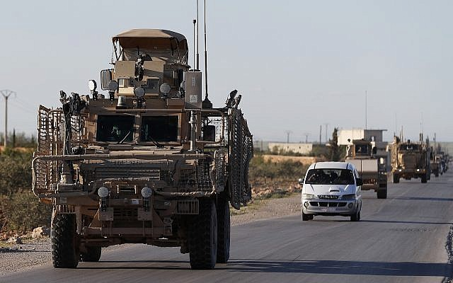A convoy of US troops drive along a road leading to the front line with Turkish-backed fighters in north Syria, March 31, 2018. (AP Photo/Hussein Malla, File)
