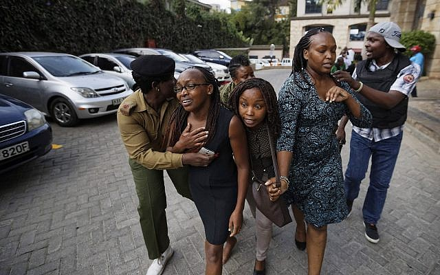 Civilians flee the scene in Nairobi, Kenya, on Tuesday, January 15, 2019, after terrorists from the Shabaab group attacked the upscale hotel complex. (AP Photo/Ben Curtis)