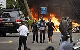 Security forces help civilians flee the scene as cars burn behind, at a hotel complex in Nairobi, Kenya Tuesday, Jan. 15, 2019. (AP Photo/Ben Curtis)