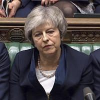 Britain's Prime Minister Theresa May listens to Labour leader Jeremy Corbyn speaking after losing a vote on her Brexit deal, in the House of Commons, London, Tuesday Jan. 15, 2019.  British lawmakers have plunged Brexit into chaos and the U.K. politics into crisis by rejecting May's divorce deal with the European Union. The 432 to 202 vote in the House of Commons was widely expected but still devastating for May, whose fragile leadership is now under siege. (House of Commons/PA via AP)
