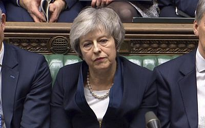 Britain's Prime Minister Theresa May listens to Labour leader Jeremy Corbyn speaking after losing a vote on her Brexit deal, in the House of Commons, London, Jan. 15, 2019 (House of Commons/PA via AP)