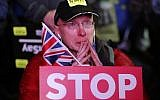 An anti-Brexit demonstrator cries as he gathers in Parliament square in London, Tuesday, Jan. 15, 2019. British lawmakers have rejected Prime Minister Theresa May's Brexit deal by a huge margin, plunging UK politics into crisis 10 weeks before the country is due to leave the European Union. (AP Photo/Frank Augstein)