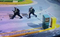 In this grab taken from security camera footage released to the local media, heavily armed attackers walk in the compound of a hotel, in Nairobi, Kenya, on January 15, 2019. (Security Camera Footage via AP)