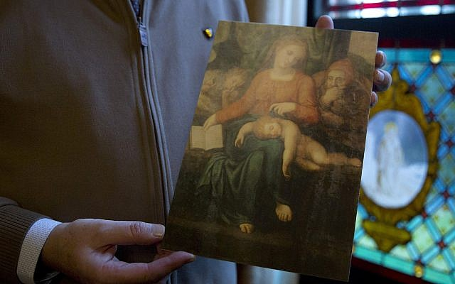 Pastor of the Sint-Ludgeruskerk, Jan Van Raemdonck holds a photo copy of the work Madonna del Silenzio in his office in Zele, Belgium, Tuesday, Jan. 15, 2019. (AP/Virginia Mayo)