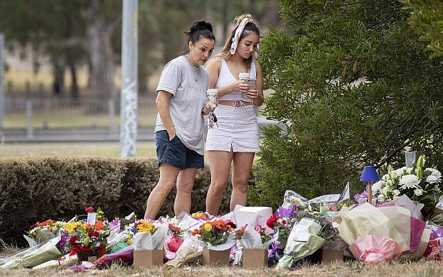 Two women stand at a floral tribute on January 18, 2019, at the scene where the body of Israeli student Aiia Maasarwe was found earlier in the week in Melbourne, Australia. (Ellen Smith/AAP Image via AP)