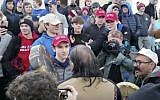 "In this January 18, 2019 image made from video provided by the Survival Media Agency, a teenager wearing a ""Make America Great Again"" hat, center left, stands in front of an elderly Native American singing and playing a drum in Washington. (Survival Media Agency via AP)"