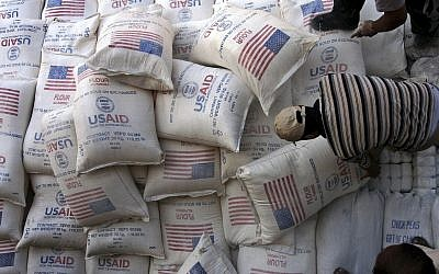 In this June 4, 2008 photo, Palestinians unload bags of flour donated by the United States Agency for International Development, USAID, at a depot in the West Bank village of Anin near Jenin. (AP Photo/Mohammed Ballas, File)