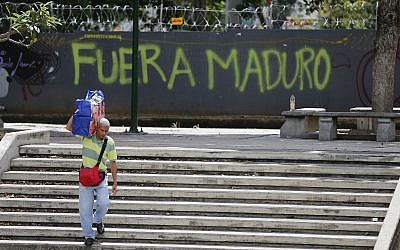 "A man walks past graffiti on the wall of a vacant lot that reads in Spanish: ""Get out Maduro,"" referring to President Nicolas Maduro in Caracas, Venezuela, Thursday, Jan. 24, 2019. (AP/Fernando Llano)"