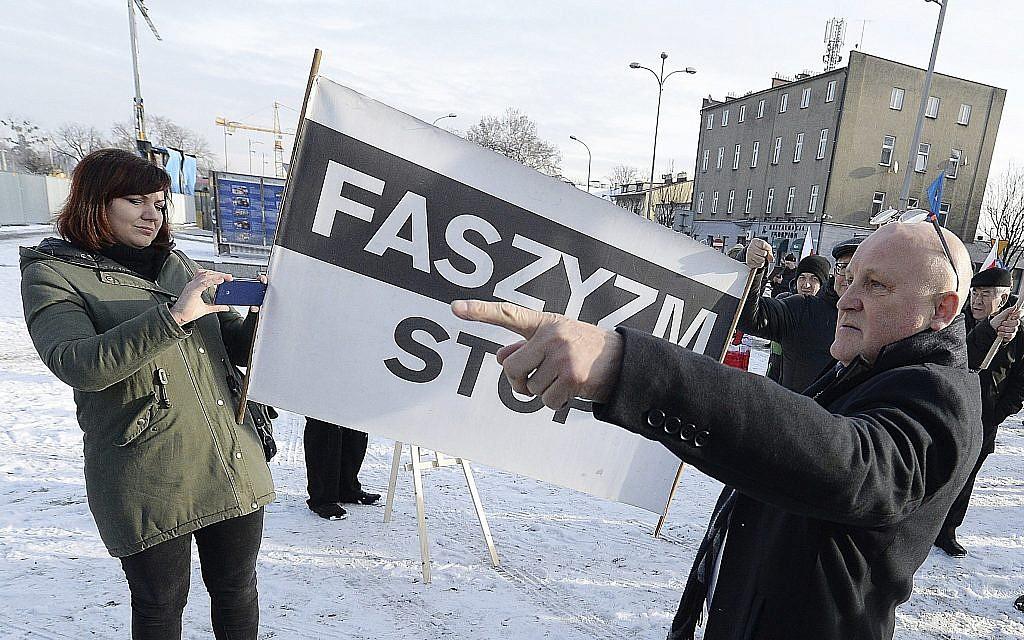 A Polish far-right activist, Piotr Rybak,right, and other nationalists gather outside the memorial site of Auschwitz in Oswiecim, Poland, on Sunday Jan. 27, 2019. (AP Photo/Czarek Sokolowski)