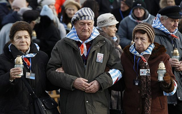 Survivors of Auschwitz, at the International Monument to the Victims of Fascism at the former Nazi concentration and extermination camp KL Auschwitz II-Birkenau, walk to place candles on International Holocaust Remembrance Day in Oswiecim, Poland, January 27, 2019. (Czarek Sokolowski/AP)