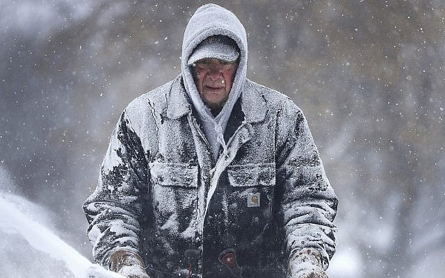 Gary Verstegen clears a sidewalk as a winter storm moves through Wisconsin on Monday, January 28, 2019, in Little Chute, Wisconsin. (William Glasheen/The Post-Crescent via AP)