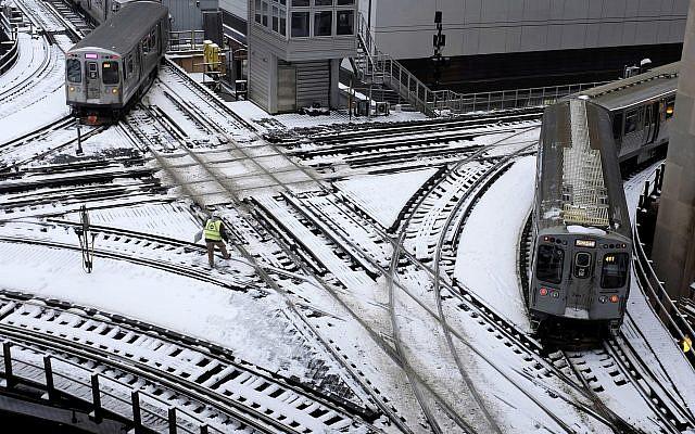 Chicago's El trains move along snow-covered tracks Monday, January 28, 2019, amid plunging temperatures. (AP Photo/Kiichiro Sato)