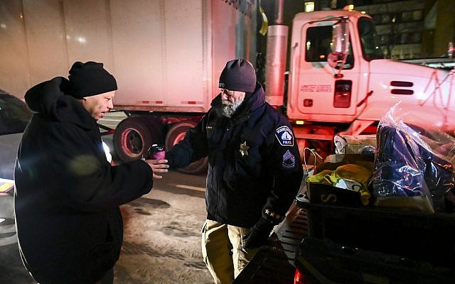Minneapolis Police Sgt. Grant Snyder, right, hands a cup of hot chocolate to Dawone Boclair outside the public library on Hennepin Avenue in downtown Minneapolis, Minnesota, as temperatures dip well below freezing, Tuesday, January 29, 2019. (Aaron Lavinsky/Star Tribune via AP)