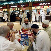 Muslim pilgrims eat their dinner at a fast food restaurant in Mecca, late Wednesday, Dec. 19, 2007. (AP/Hasan Sarbakhshian)