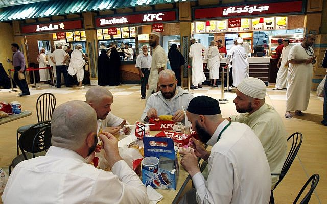 Muslim pilgrims eat their dinner at a fast food restaurant in Mecca, late Wednesday, Dec. 19, 2007. (AP/Hasan Sarbakhshian)