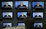 Illustrative: A man watches Prime Minister Benjamin Netanyahu making a speech on television screens at a shop in Jerusalem, on June 14, 2009. (AP/Bernat Armangue/File)