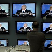 Illustrative: An Israeli man looks at Prime Minister Benjamin Netanyahu making a speech on television screens at a shop in Jerusalem, Sunday June 14, 2009. (AP/Bernat Armangue)