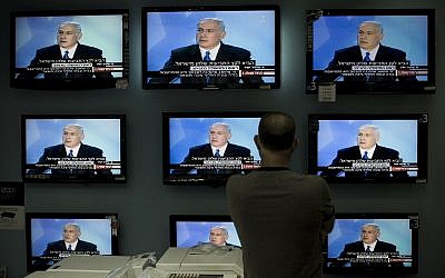 Illustrative: An Israeli man watches Prime Minister Benjamin Netanyahu making a speech on television screens at a shop in Jerusalem, on June 14, 2009. (AP/Bernat Armangue/File)