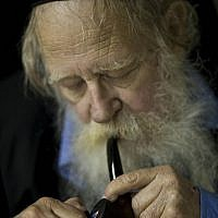 In this file photo taken on Nov. 10, 2010, Rabbi Adin Steinsaltz smokes a pipe during an interview with The Associated Press in Jerusalem. The 73-year-old rabbinical scholar had just completed a monumental 45-year project hailed in Jewish scholarly circles as a breakthrough of biblical proportions, the most comprehensive translation and commentary of the Talmud, with its 63 basic sections and nearly 6,000 pages. (AP Photo/Bernat Armangue, File)