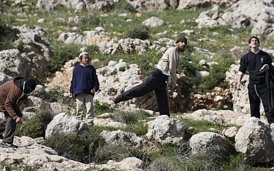 Illustrative: Jewish settlers throw stones near the West Bank village of Hawara, after five people were killed in the nearby Jewish settlement of Itamar Saturday, March 12, 2011. (AP Photo/Nasser Ishtayeh)