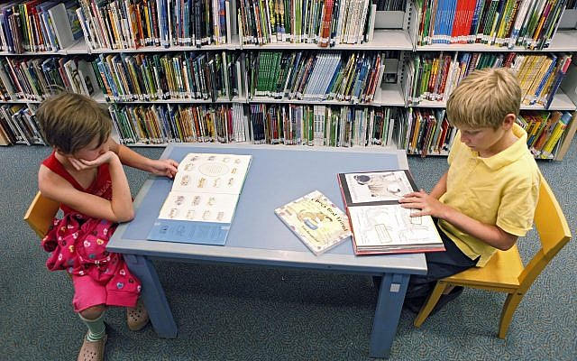 ILLUSTRATIVE -- In this photo taken on June 20, 2011, Nine year old Grace Powers, left, and her brother James, 11, read in the children's section at the Denver Public Library (AP Photo/Ed Andrieski)