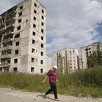Illustrative: An Abkhazian man walks past war-damaged apartment buildings in Sukhumi, the capital of the Georgian breakaway region of Abkhazia, on August 25, 2011. (AP Photo/Mikhail Metzel)