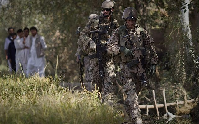Afghan men watch German Army soldiers patroling near Char Darah, outside Kunduz, Afghanistan, September 20, 2011. (Anja Niedringhaus/AP)