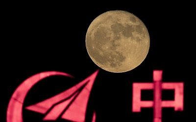 In this photo taken Tuesday, Nov. 15, 2016, the supermoon rises over a logo for AVIC, or Aviation Industry Corp, a state owned enterprise involved in China's manned space mission in Beijing. (AP Photo/Ng Han Guan)
