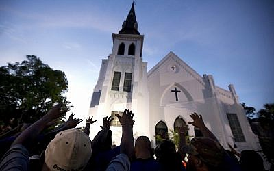 In this Friday, June 19, 2015 file photo a crowd of people pray  outside the Emanuel AME Church, after a memorial for the nine people killed by Dylann Roof in Charleston, S.C. .(AP Photo/Stephen B. Morton)