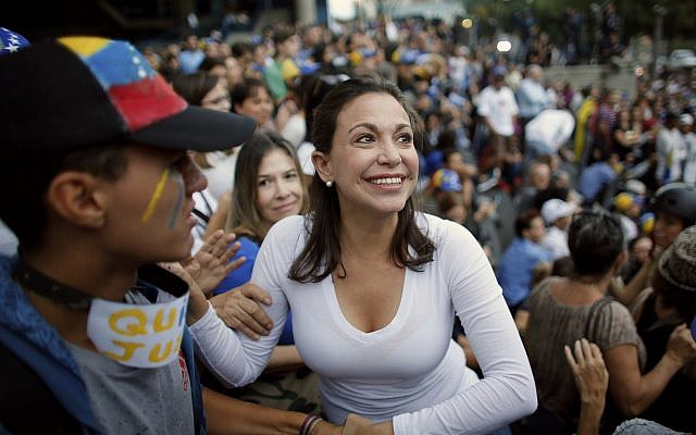 Opposition leader Maria Corina Machado, a former lawmaker, greets supporters during a vigil in honor of those who have been killed during clashes between security forces and demonstrators in Caracas, Venezuela, on July 31, 2017. (AP Photo/Ariana Cubillos)