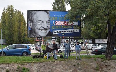 In this Oct. 5, 2017 file photo, activists from the Egyutt (Together) opposition party in Hungary stand in front of billboards of the government's campaign against George Soros and his support for migration in Budapest. (AP/Pablo Gorondi)