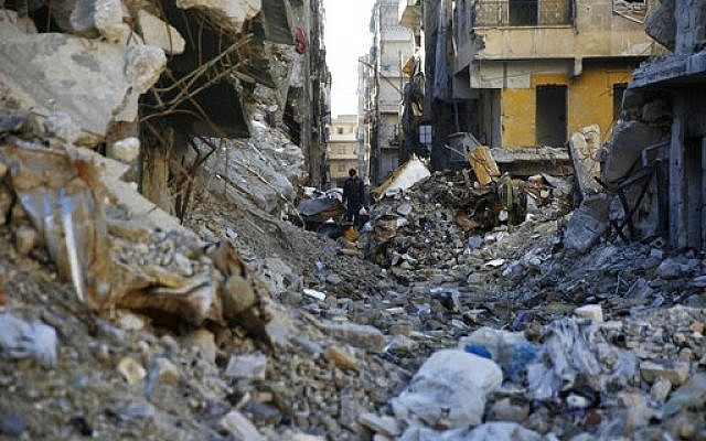 A Syrian walks through the destruction of the Salaheddine neighborhood in the eastern Aleppo, Syria, Saturday, Jan. 20, 2018. (AP Photo/Hassan Ammar)