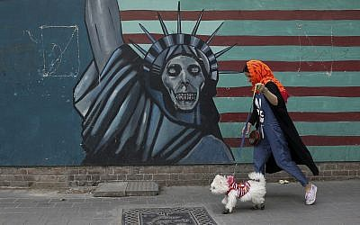 A woman walks her dog past an anti-US mural painted on the wall of the former US Embassy in Tehran, May, 2018 (AP Photo/Vahid Salemi)