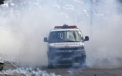 File: A Palestinian ambulance emerges from a cloud of tear gas during clashes between Palestinians and Israeli forces in the West Bank city of Bethlehem, Tuesday, May 15, 2018 (AP Photo/Majdi Mohammed)