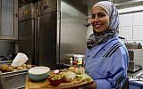 In this photo from November 9, 2018, Malakeh Jazmati carries food in her restaurant in Berlin, Germany. (AP Photo/Jona Kallgren)