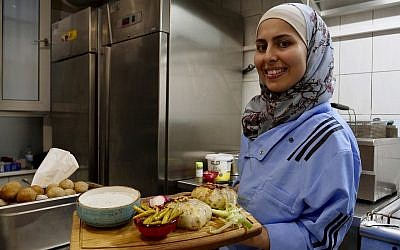 In this photo from November 9, 2018, Malakeh Jazmati carries food in her restaurant in Berlin, Germany. (AP Photo/Jona Kallgren)