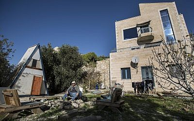 In this photo from January 17, 2016, Moshe Gordon sits outside his guest house advertised on the Airbnb international home-sharing site in Nofei Prat settlement in the West Bank. (AP Photo/Tsafrir Abayov, File)