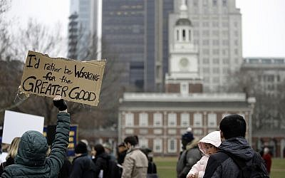 Furloughed federal worker Meghan Powell, holding sign on left, demonstrates with others against the partial government shutdown in view of Independence Hall in Philadelphia, Tuesday, Jan. 8, 2019. (AP Photo/Matt Rourke)
