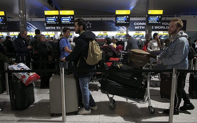 Passengers wait in a queue in departures at Heathrow Airport in London, Tuesday, Jan. 8, 2019. London's Heathrow Airport briefly halted departing flights on Tuesday after a reported drone sighting — a development that came just three weeks after multiple reports of drone sightings caused travel chaos at nearby Gatwick Airport. (Yui Mok/PA via AP)