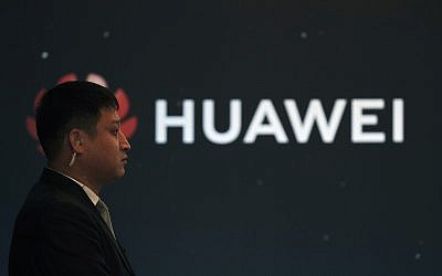 In this Jan. 9, 2019, photo, a security guard stands near the Huawei company logo during a new product launching event in Beijing (AP Photo/Andy Wong)